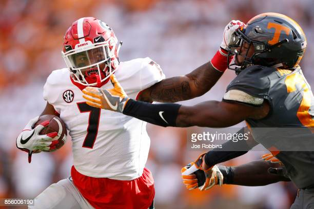 Andre Swift of the Georgia Bulldogs runs the ball against Micah Abernathy of the Tennessee Volunteers in the second quarter of a game at Neyland...