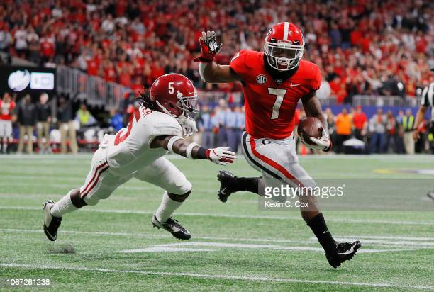 Andre Swift of the Georgia Bulldogs scores an 11yard receiving touchdown in the second quarter as Shyheim Carter of the Alabama Crimson Tide is...