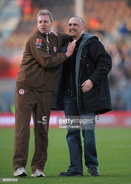 Andre Trulsen assistance trainer of St Pauli congratulates Holger Stanislawski trainer of St Pauli during the Second Bundesliga match between FC St...