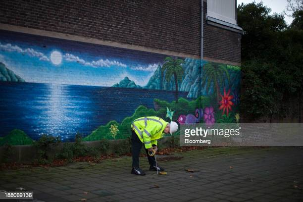 Andre van Krieken a 69yearold employed via specialist seniors recruitment company 65plus lowers a tape measure into a pavement access hole as he...