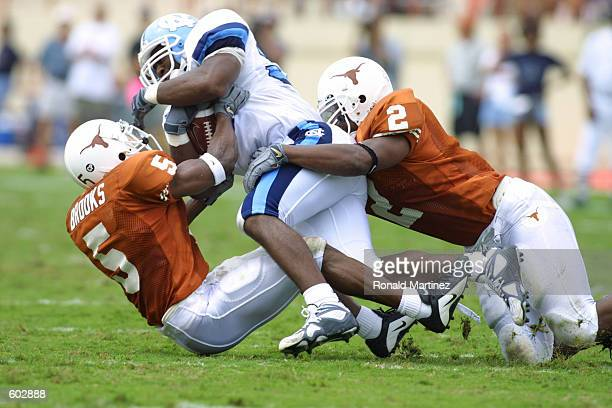 Andre Williams of North Carolina is tackled by Ahmad Brooks and Everick Rawls of the Texas Longhorns during the game at RoyalTexas Memorial Stadium...