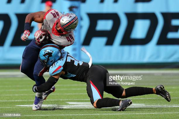 Andre Williams of the Houston Roughnecks is hit by Derron Smith of the Dallas Renegades at an XFL football game on March 01, 2020 in Arlington, Texas.