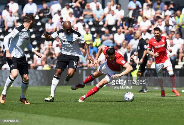 Andre Wisdom of Derby County tackles Keifer Moore of Barnsley during the Sky Bet Championship match between Derby County and Barnsley at iPro Stadium...