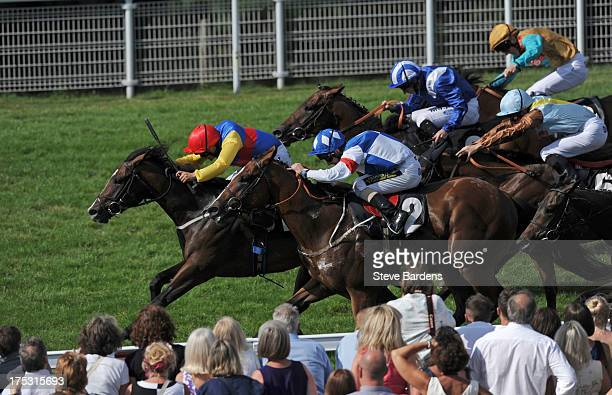 Andrea Atzeni riding Flying Bear leads the field during the Golf at Goodwood Nursery Stakes at Goodwood racecourse on August 02 2013 in Chichester...