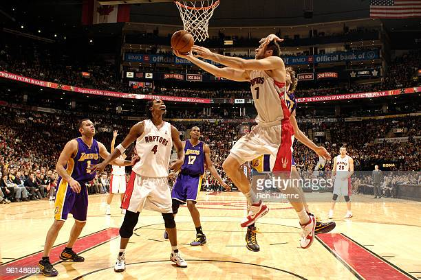 Andrea Bargnani of the Toronto Raptors drives baseline for the reverse and gets a hand on his head from Pau Gasol of the Los Angeles Lakers during a...