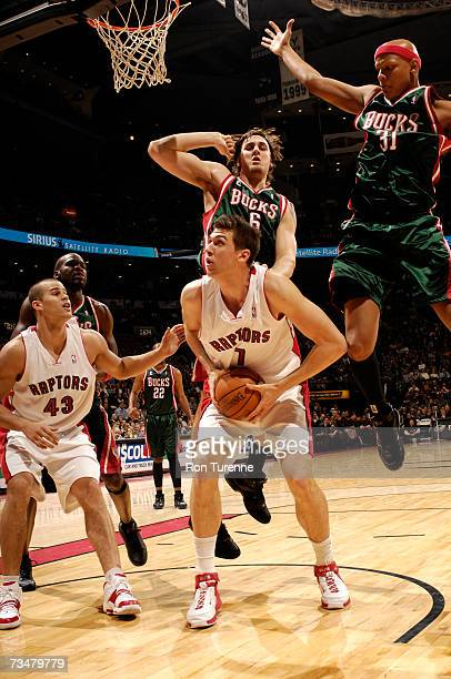 Andrea Bargnani of the Toronto Raptors is about to take a shot against the defense of Charlie Villanueva and Andrew Bogut of the Milwaukee Bucks on...