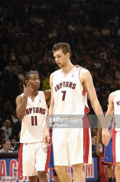 Andrea Bargnani of the Toronto Raptors listens to instructions by teammate TJ Ford during a game against the New York Knicks at Air Canada Centre on...