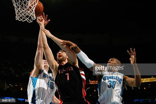 Andrea Bargnani of the Toronto Raptors tries to make a shot between Sean Marks and David West of the New Orleans Hornets on February 6 2009 in New...