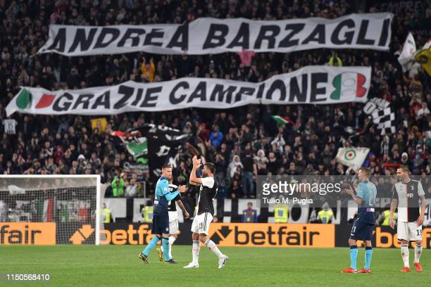 Andrea Barzagli of Juventus leaves the pitch greeting supporters as they lift a banner to farewell him during the Serie A match between Juventus and...