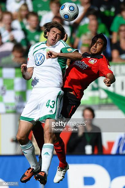 Andrea Barzagli of Wolfsburg and Arturo Vidal of Leverkusen jump for a header during the Bundesliga match between VfL Wolfsburg and Bayer Leverkusen...
