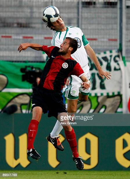 Andrea Barzagli of Wolfsburg jumps for a header with Marcel Ziemer of WehenWiesbaden during the DFB Cup first round match between SV WehenWiesbaden...