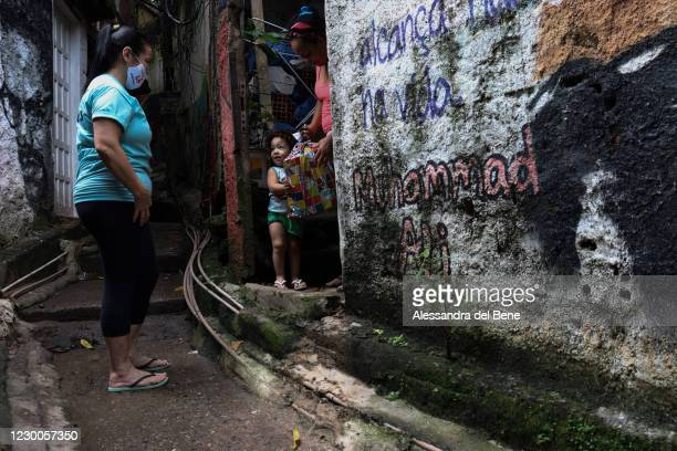 Andrea Belone, a cook at Uniao de Mulheres Pro Melhoramentos da Roupa Suja Kindergarten, delivers Christmas presents for children of Roupa Suja in...