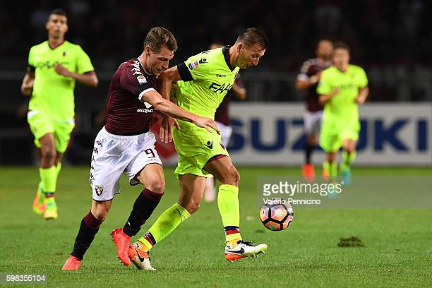 Andrea Belotti of FC Torino competes with DanieleÊGastaldello of Bologna FC during the Serie A match between FC Torino and Bologna FC at Stadio...