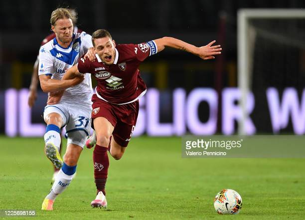 Andrea Belotti of Torino FC is challenged by Birkir Bjarnason of Brescia Calcio during the Serie A match between Torino FC and Brescia Calcio at...