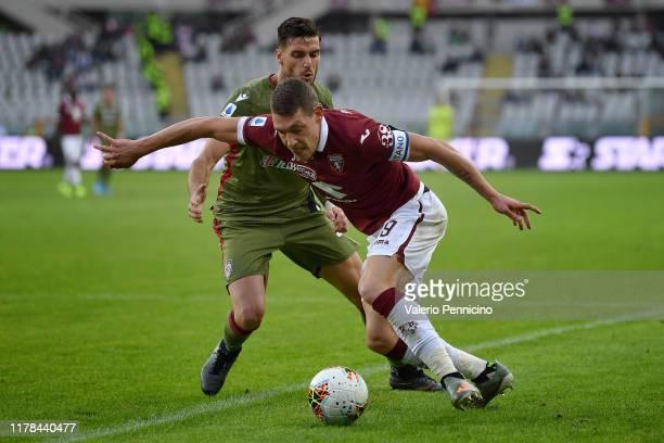 Andrea Belotti of Torino FC is challenged by Luca Ceppitelli of Cagliari Calcio during the Serie A match between Torino FC and Cagliari Calcio at...