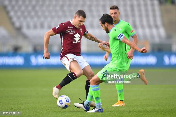 Andrea Belotti of Torino FC is challenged by Marco Parolo of SS Lazio during the Serie A match between Torino FC and SS Lazio at Stadio Olimpico di...