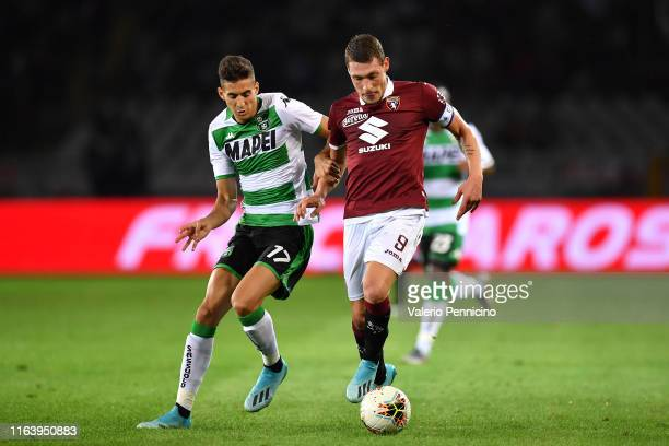 Andrea Belotti of Torino FC is challenged by Mert Muldur of US Sassuolo during the Serie A match between Torino FC and US Sassuolo at Stadio Olimpico...