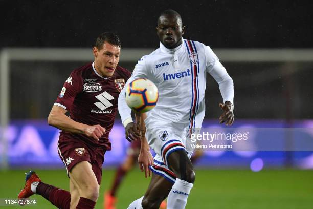 Andrea Belotti of Torino FC is challenged by Omar Colley of UC Sampdoria during the Serie A match between Torino FC and UC Sampdoria at Stadio...