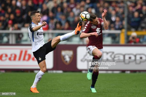 Andrea Belotti of Torino FC is tackled by Ivan Perisic of FC Internazionale during the Serie A match between Torino FC and FC Internazionale at...