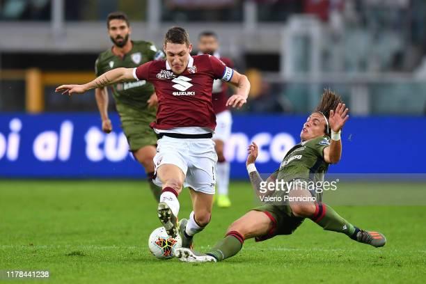 Andrea Belotti of Torino FC is tackled by Luca Pellegrini of Cagliari Calcio during the Serie A match between Torino FC and Cagliari Calcio at Stadio...
