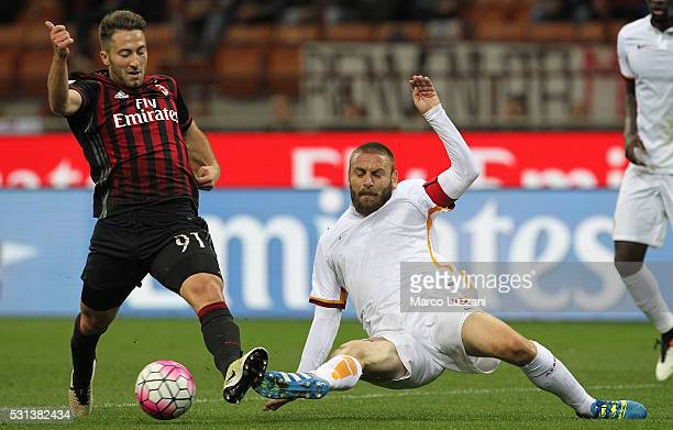 Andrea Bertolacci of AC Milan is challenged by Daniele De Rossi of AS Roma during the Serie A match between AC Milan and AS Roma at Stadio Giuseppe...