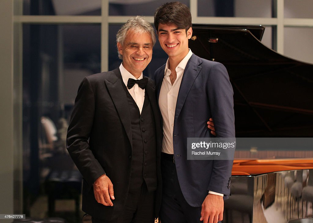 Andrea Bocelli and son Matteo Bocelli break away from the guests for a moment together at the piano during Alfred Mann Foundation's an Evening Under The Stars with Andrea Bocelli on June 8, 2015 in Los Angeles, California.