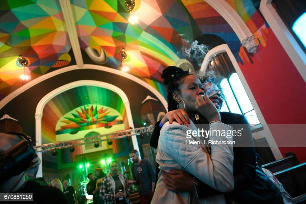 Andrea Camp left of Chicago hugs Kimm Miller right from Lakewood as she smokes from a pipe as the two participate in 4/20 celebration services at the...