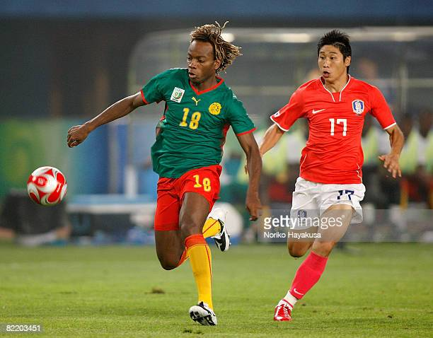 Andrea Consigli of Cameroon and Lee Keun Ho of South Korea compete for the ball during the Men's Group D match between South Korea and Cameroon on...