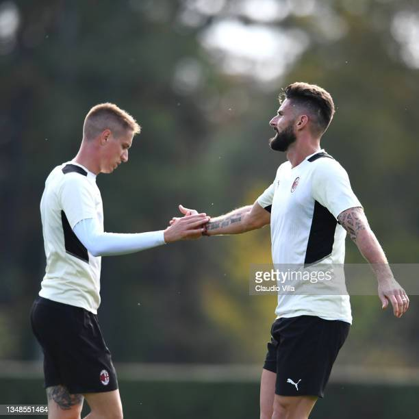 Andrea Conti and Olivier Giroud of AC Milan in action during an AC Milan training session at Milanello on October 24, 2021 in Cairate, Italy.