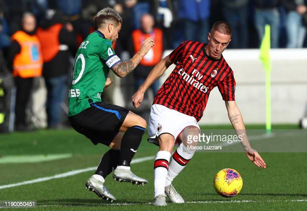 Andrea Conti of AC Milan competes for the ball with Alejandro Dario Gomez of Atalanta BC during the Serie A match between Atalanta BC and AC Milan at...