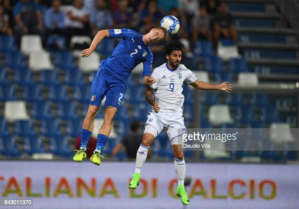 Andrea Conti of Italy competes for the ball with Lior Refaelov of Israel during the FIFA 2018 World Cup Qualifier between Italy and Israel at Mapei...
