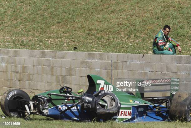 Andrea de Cesaris of Italy sits on the wall and surveys the damage to the Team 7up Jordan Jordan 191 Ford HB 35 V8 after crashing out of the British...
