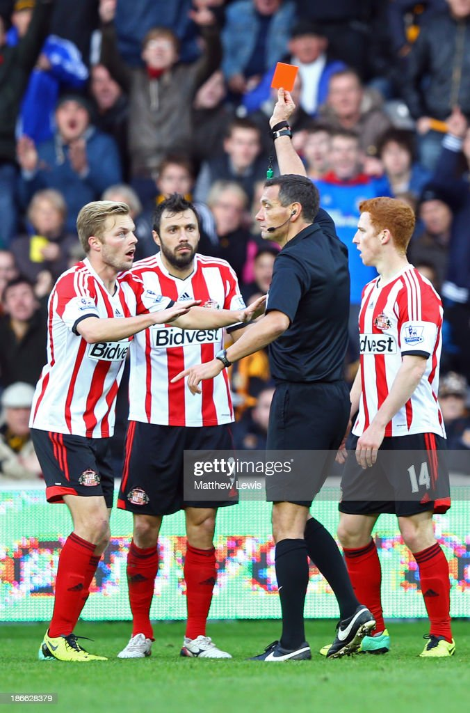 Andrea Dossena (C) of Sunderland is sent off with a red card by referee Andre Marriner as team-mate Sebastian Larsson (L) protests during the Barclays Premier League match between Hull City and Sunderland at KC Stadium on November 2, 2013 in Hull, England.