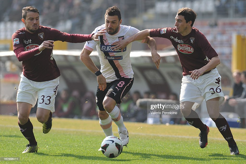 Andrea Dossena (C) of US Citta di Palermo is challenged by Matteo Brighi (L) and Matteo Darmian of Torino FC during the Serie A match between Torino FC and US Citta di Palermo at Stadio Olimpico di Torino on March 3, 2013 in Turin, Italy.