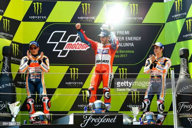 Andrea Dovizioso of Italy and Ducati Team celebrates on the podium next to Marc Marquez of Spain and Repsol Honda Team second and Dani Pedrosa of...