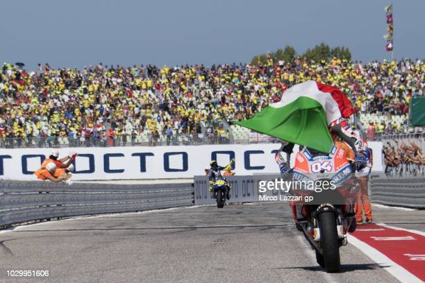Andrea Dovizioso of Italy and Ducati Team celebrates the victory with flag at the end of the MotoGP race during the MotoGP of San Marino Race at...