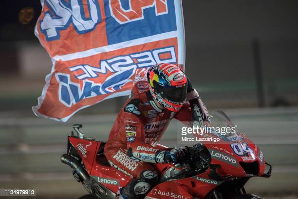 Andrea Dovizioso of Italy and Ducati Team celebrates with flag the victory at the end of the MotoGP race during the MotoGP of Qatar Race at Losail...