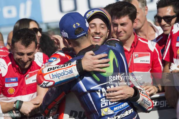 Andrea Dovizioso of Italy and Ducati Team celebrates with Maverick Vinales of Spain and Movistar Yamaha MotoGP under the podium at the end of the...