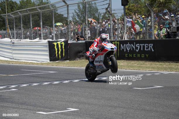 Andrea Dovizioso of Italy and Ducati Team cuts the finish lane and celebrates the victory at the end of the MotoGP race during the MotoGp of...