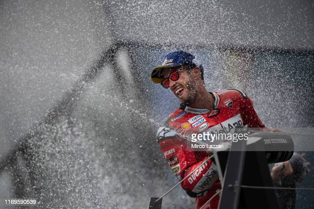 Andrea Dovizioso of Italy and Ducati Team greets the fans and celebrates the victory on the podium with Prosecco at the end of the MotoGp race during...