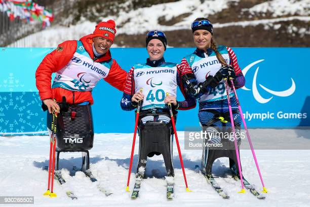 Andrea Eskau of Germany second place Kendall Gretsch of the United States first place and Oksana Masters of the United States third place pose for...