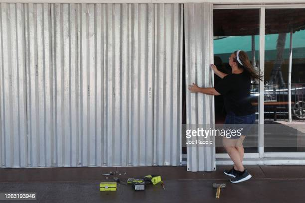 Andrea Hagopian puts shutters over the sliding glass doors at Maria's Restaurant as Hurricane Isaias approaches on August 01, 2020 in Stuart,...