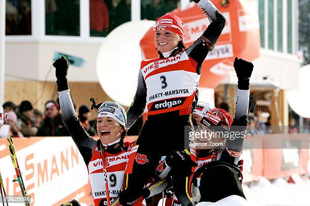 Andrea Henkel of Germany celebrates winning the Women's Mass Start event with Katrin Hitzer and Magdalena Glagow of Germany during the IBU Biathlon...