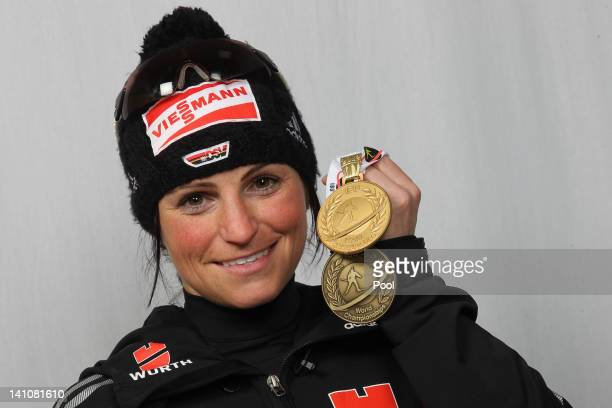 Andrea Henkel of Germany shows her medals of the Women's 4 x 6km Relay during the IBU Biathlon World Championships at Chiemgau Arena on March 10,...