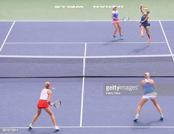 Andrea Hlavackova of the Czech Republic hits an overhead as partner Monica Niculescu of Romania looks on as Kristina Mladenovic of France and Timea...