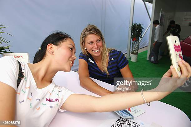 Andrea Hlavackova of the Czech Republic poses for photos with a fan on day five of 2014 Dongfeng Motor Wuhan Open at Optics Valley International...
