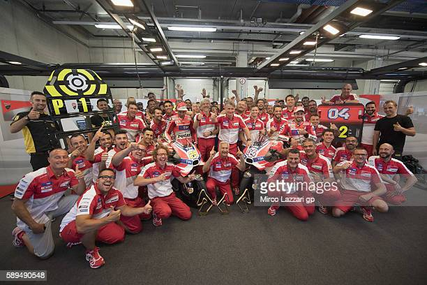 Andrea Iannone of Italy and Ducati Team and Andrea Dovizioso of Italy and Ducati Team celebrate with team in box the victory and the second place at...