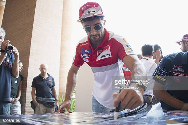 Andrea Iannone of Italy and Ducati Team signs autographs for fans during the preevent 'Street artists will connect art with motorsport' in Teatro...