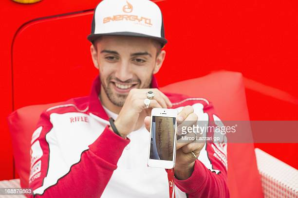 Andrea Iannone of Italy and Energy TI Pramac Racing Team shows at the mobile the picture of his scar after the operation during the MotoGp Of France...