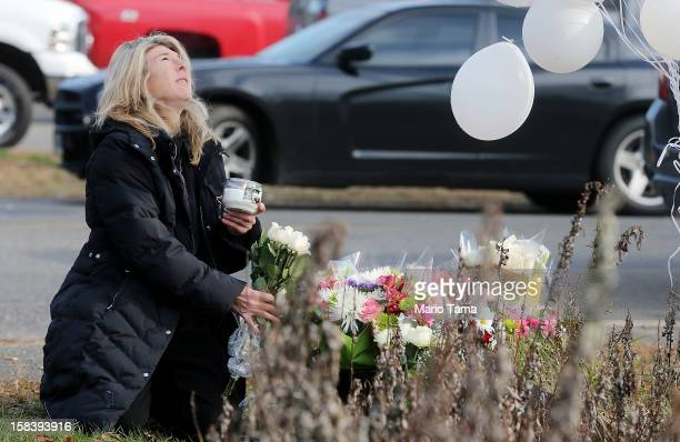 Andrea Jaeger places flowers and a candle at a makeshift memorial outside a firehouse which was used as a staging area for families following the...